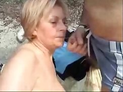 very nice mature lady is sucking a cock on the beach
